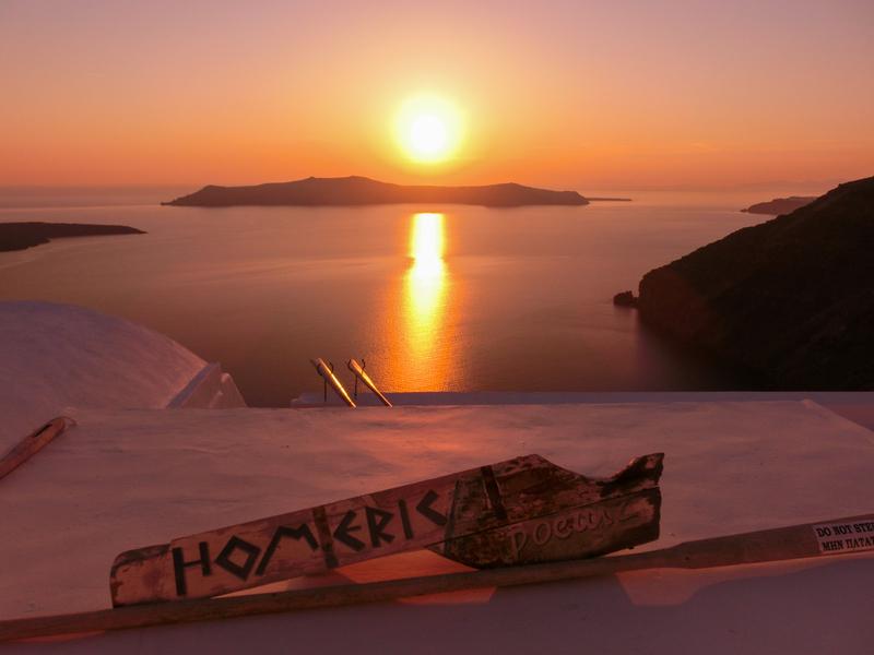 サントリーニ島のフィラの夕日でオレンジ色に染まった海