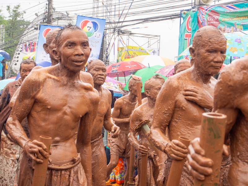 ピーターコーン祭りでピーターコーンの仮面を付けて歩く人々と全身に泥を付けた泥人間