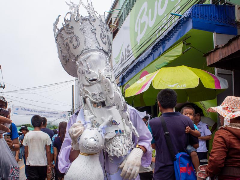 ピーターコーン祭りで白いピーターコーンの仮面を付けて歩く人々
