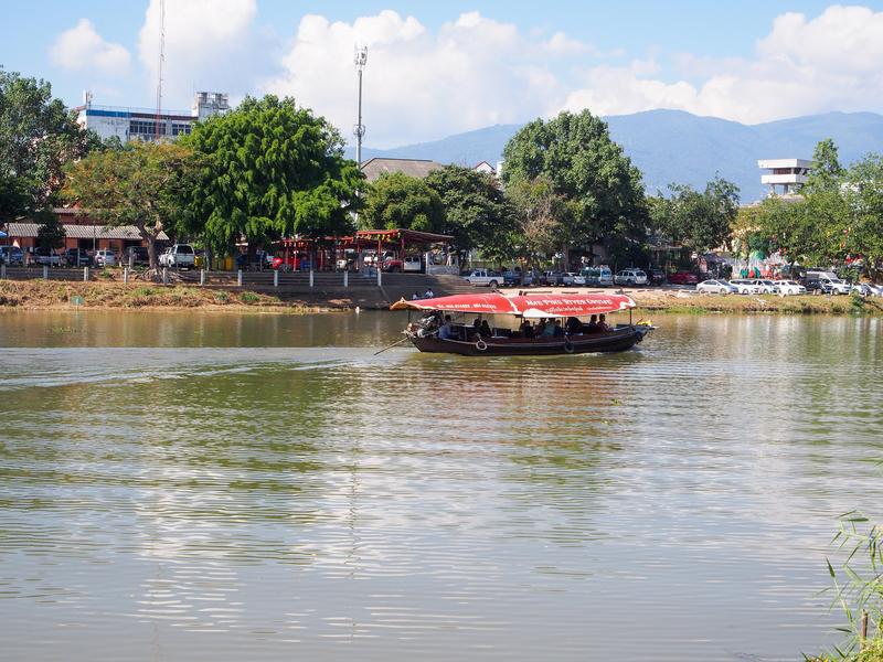 チェンマイのピン川沿いのカフェから眺める川を行きかう遊覧船