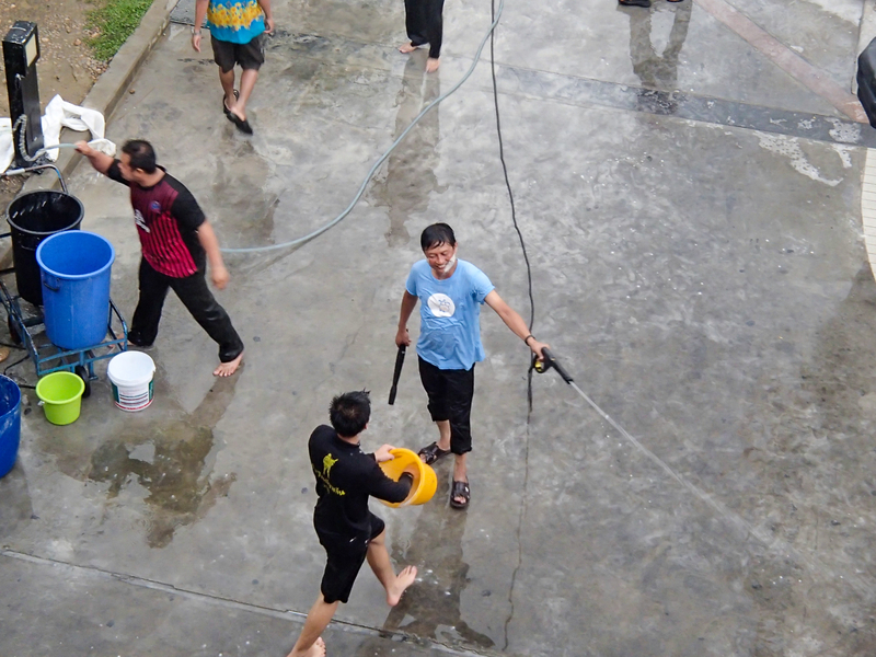 バンコクのソンクラーンでホースを使って水をかける人