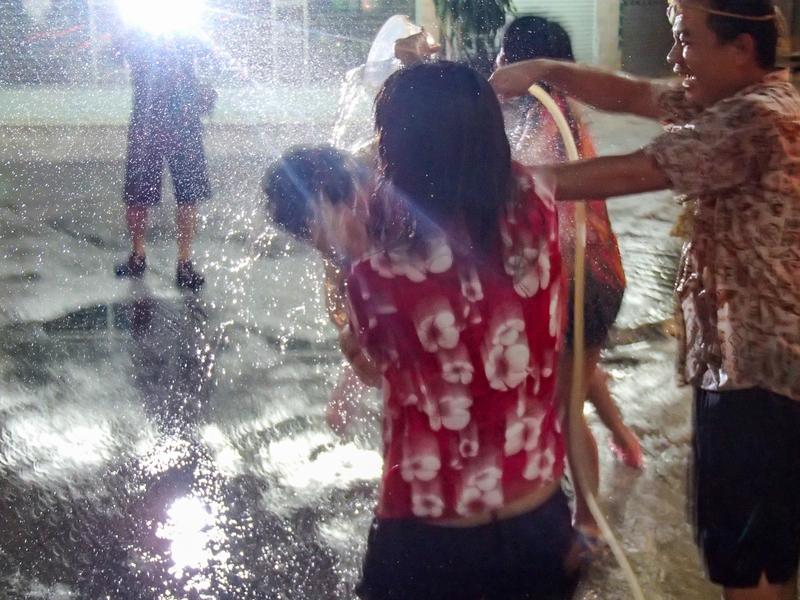 夜のスクンビット通りでホースを使って水をかける人