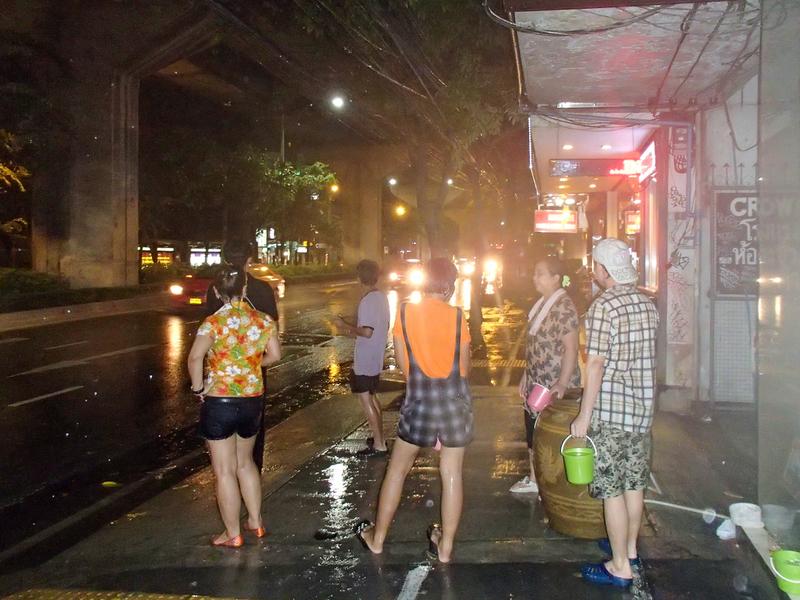 バンコクのソンクラーンで通りを歩く人やバスに水をかけようとする人々