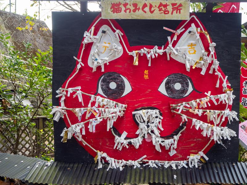 臼杵市にある福良天満宮の猫の顔をした赤いおみくじ掛け