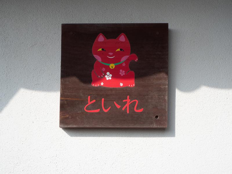 臼杵市にある福良天満宮の赤い猫が描かれたトイレの案内板