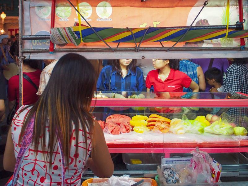 チェンマイのロイクラトン祭りのパレードが通る歩道でカットフルーツを売る屋台
