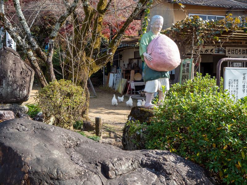 犬山市にある桃太郎神社にある桃太郎のおばあさんの人形。川へ洗濯に行ったおばあさんが両手で大きな桃を持っている