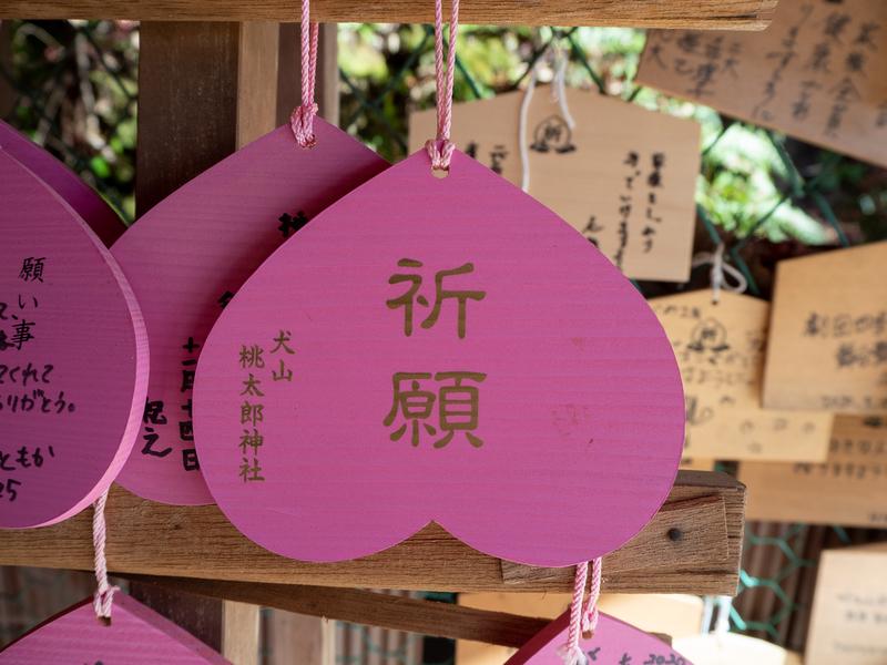 犬山市にある桃太郎神社の桃の形をした絵馬。ピンク色の絵馬に金色の文字で「祈願」と書かれている。
