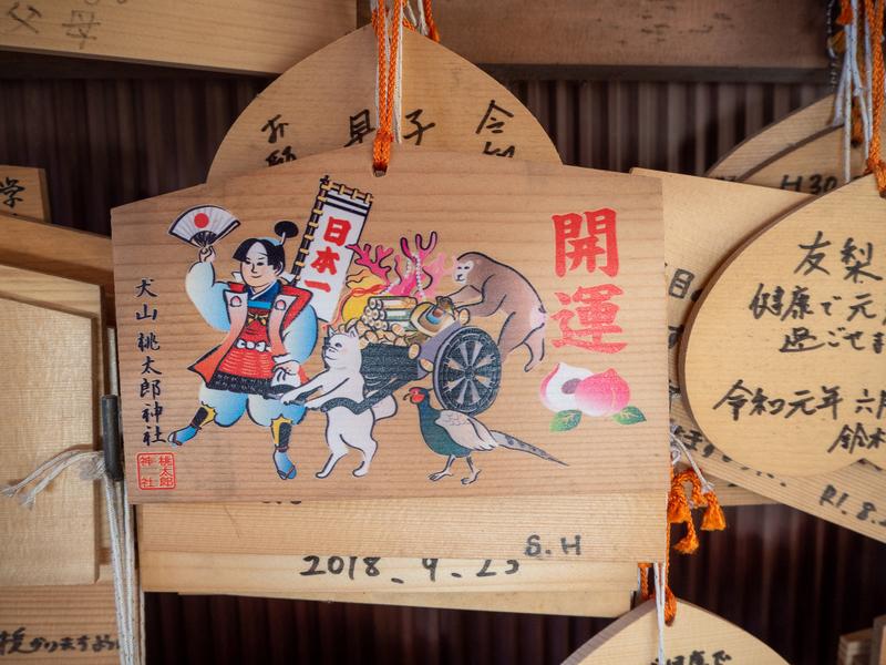 犬山市にある桃太郎神社の絵馬。桃太郎が犬と猿、雉と共に鬼退治に行く様子を描いている。絵馬には神社名と共に「開運」と書かれている。