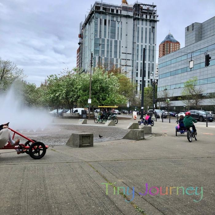 噴水の周りを走る色んな自転車