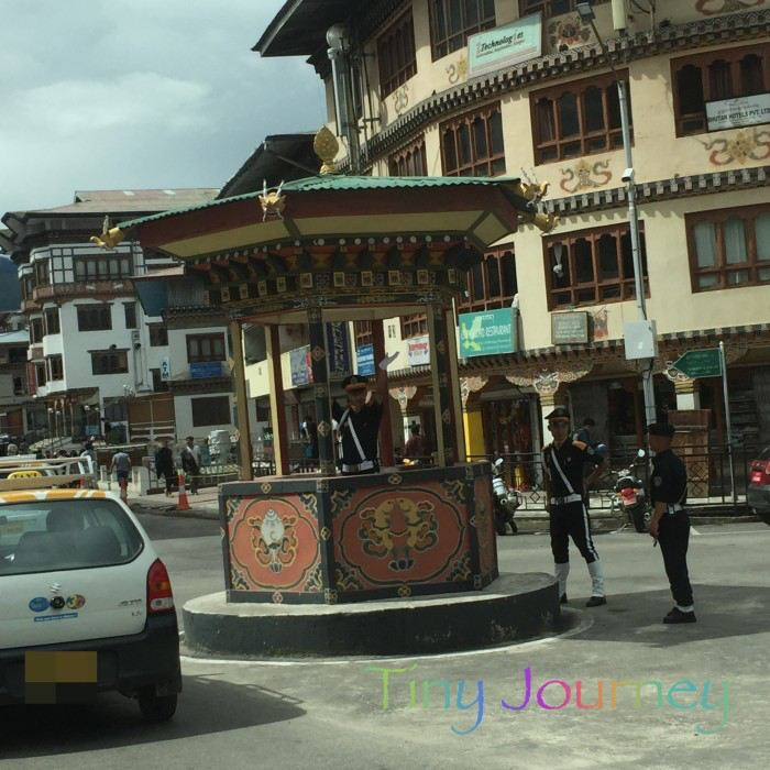 ブータンのメインストリートと手信号する警察官