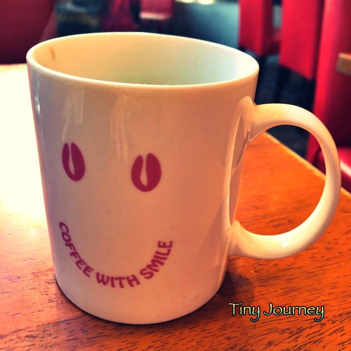 目玉がコーヒー豆のスマイルが描かれたマグカップ