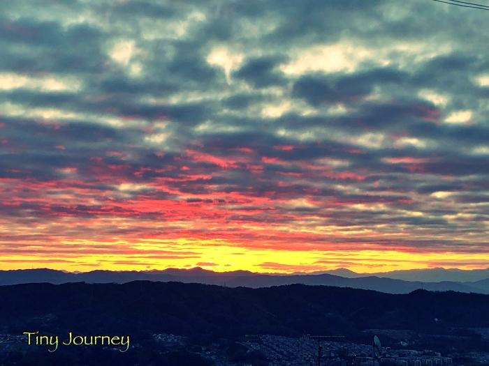 赤い日が見えだした曇り空と山の隙間