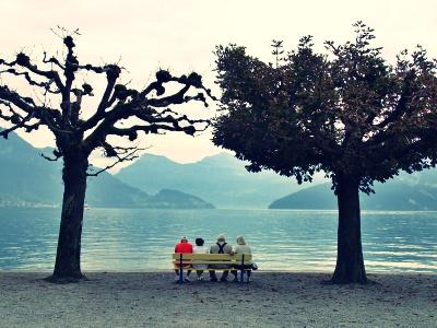 湖のほとりのベンチに仲良く座る人たち