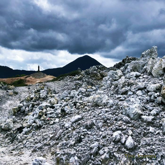 怪しい雲が広がる空と白い流紋岩が転がる地