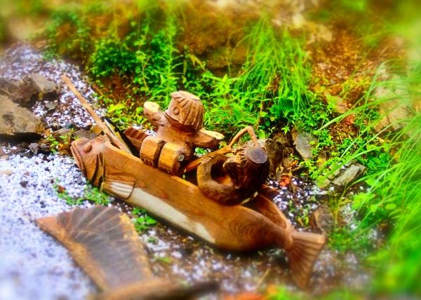 魚型の舟で遡上する木彫りの河童たち