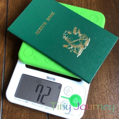 計りに乗せて計量中の測量野帳。ディスプレイには72gと表示されている。
