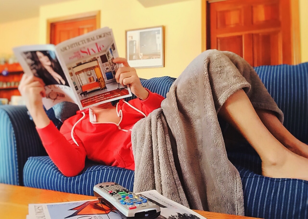 雑誌を見ながらソファでくつろぐ女性