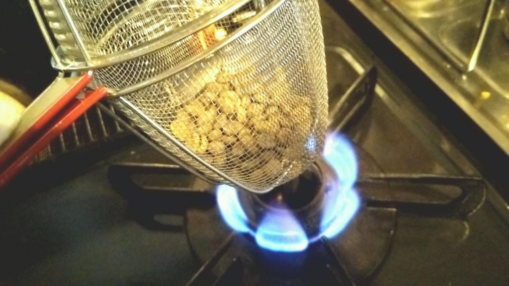 ザルに入れたコーヒー生豆をコンロで焙煎する