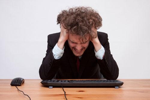 突然のパソコントラブルに頭を抱える男