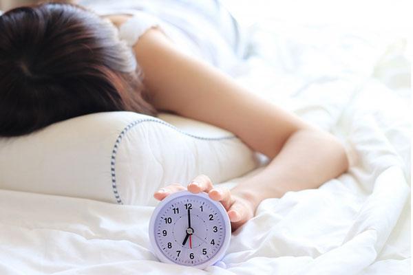目覚まし時計と眠っている女性
