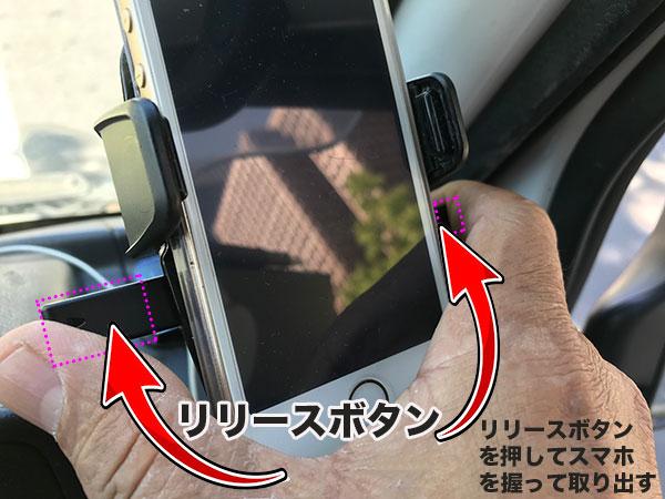 車載用スマホホルダーからスマホを取り出している画像