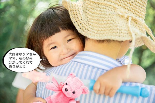 大好きなクマのぬいぐるみを持って抱っこされている子供
