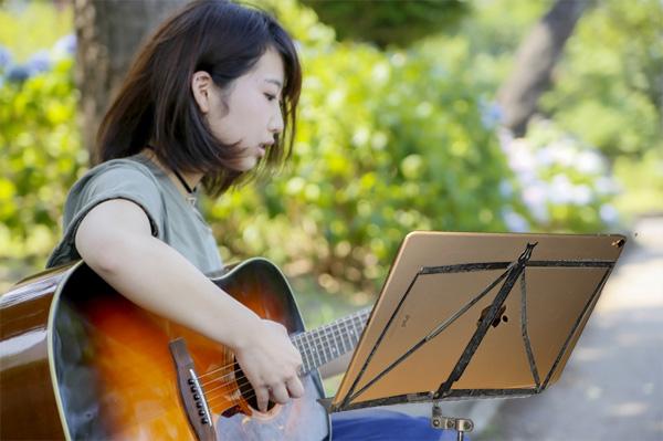 公園でiPadを使ってギター練習している女性