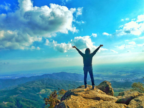 山の頂上で外界を見下ろして深呼吸する