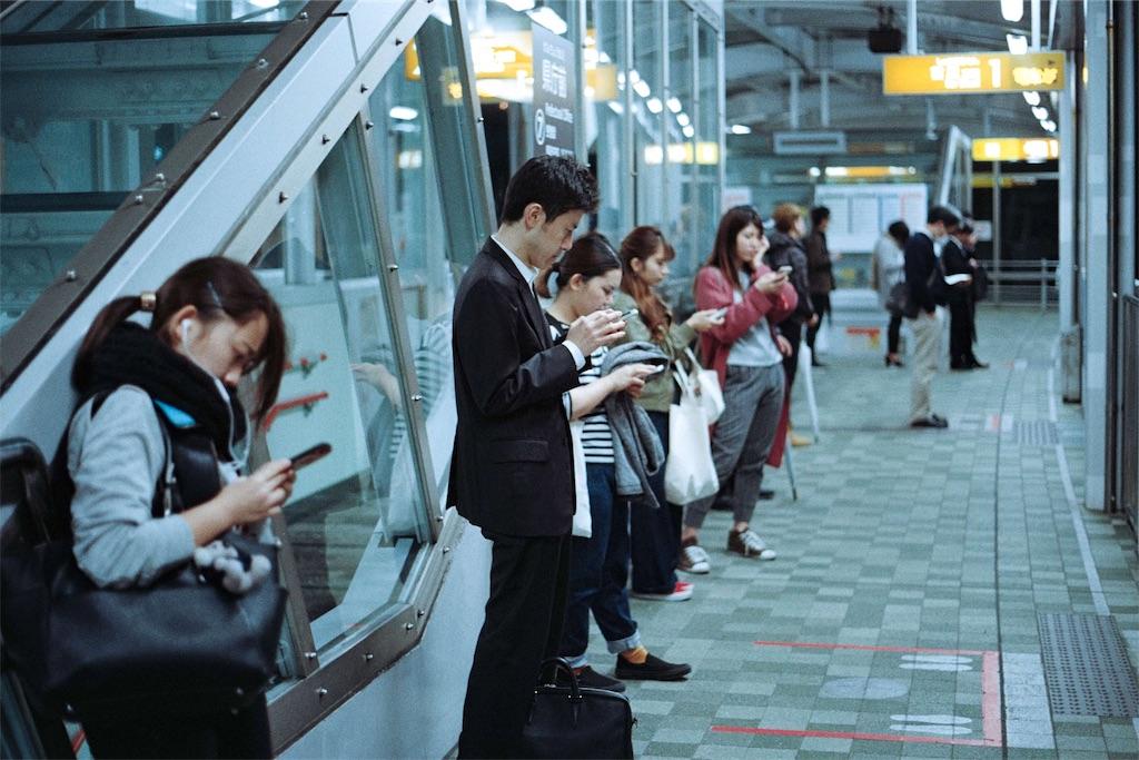 駅でスマートフォンをいじる人々