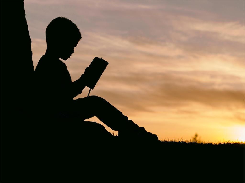 夕日の中で本を読む少年