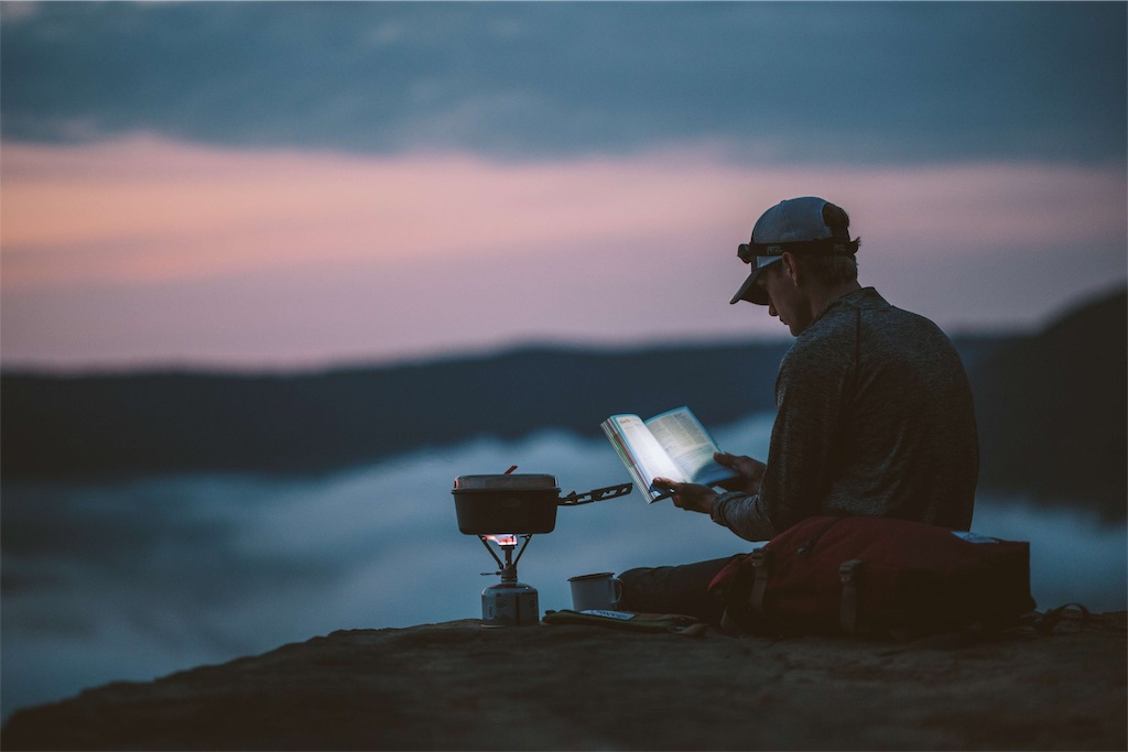 あぐらをかいて本を読む女性