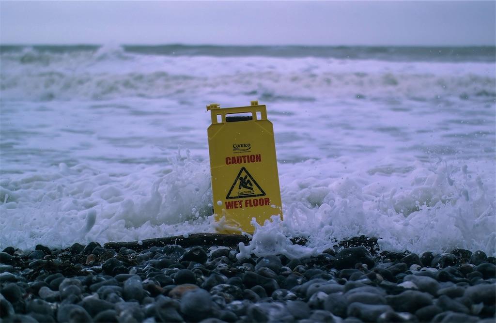 海辺で「caution」と書いてある看板が波に打たれる様子