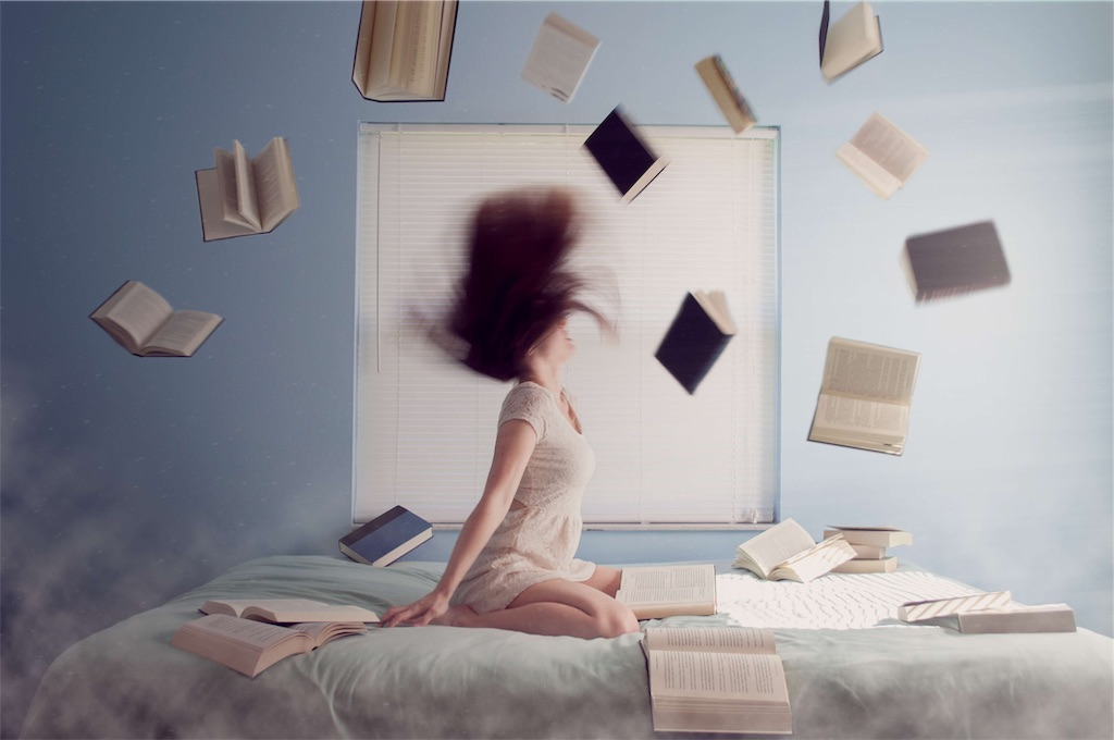 勉強が嫌になりベッドの上で本を撒き散らす女性