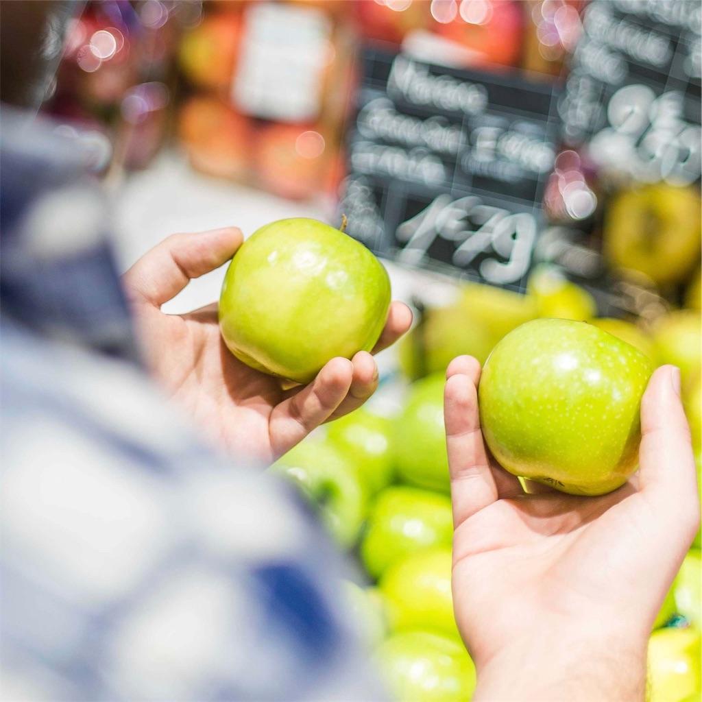 二つのリンゴを手に持って見比べている男性