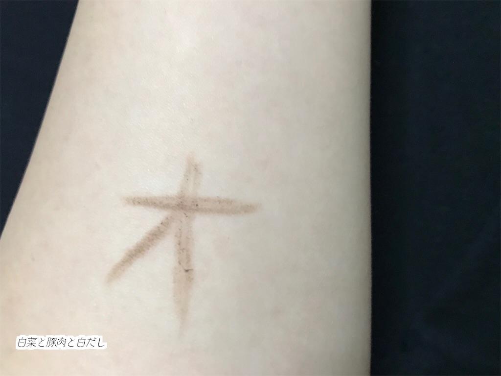 カバー力検証のため腕にアイブロウで「オ」と書いた画像