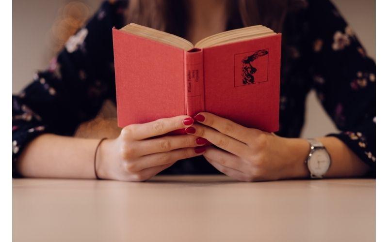 本を読み調べる女性