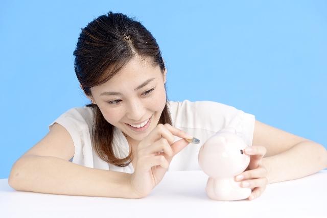 家計簿を参考に貯金していく女性