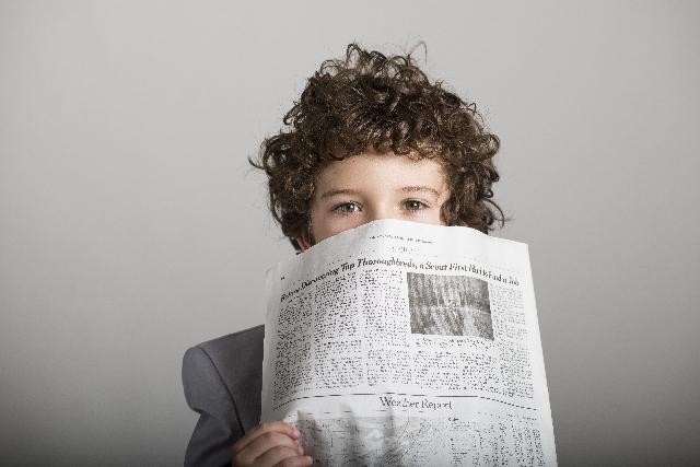 新聞を持った好奇心旺盛な少年