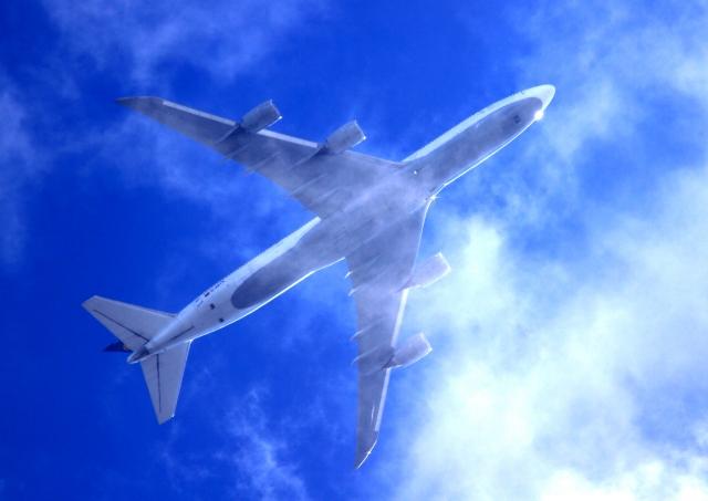 飛行機が青空を飛んで行く画像
