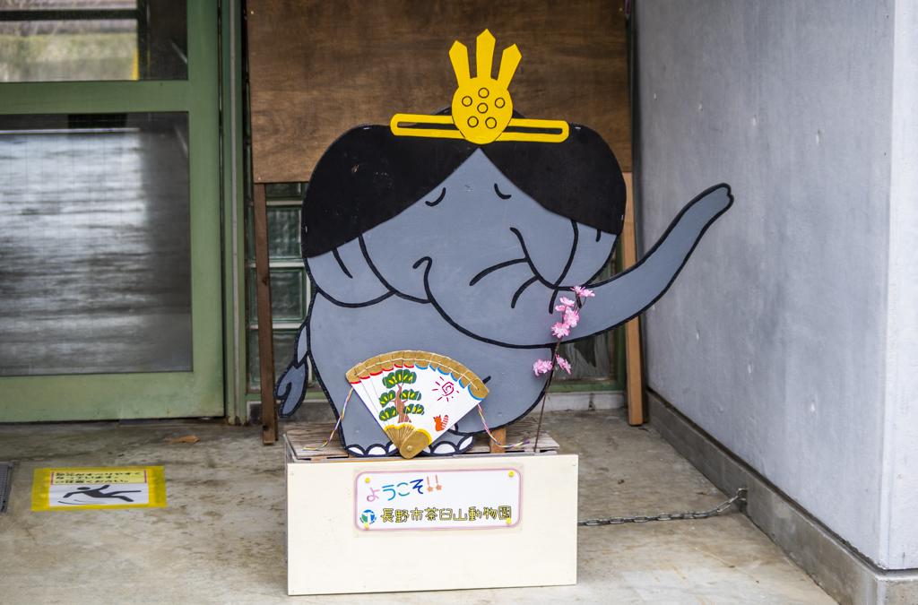 ゾウの頭の部分がお雛様の髪のかたちに黒く塗られたイラストの看板