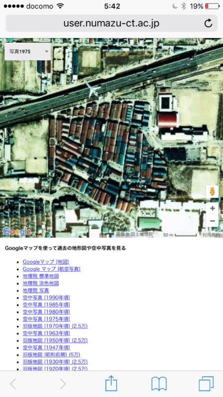 昭和50年(1975年)朝鮮人などが不法占拠した埋立地(空港敷地)に建てられた長屋(バラック)の「部落集落」の上を旅客機が低空飛行し、近くの高速道路で車が走っている。