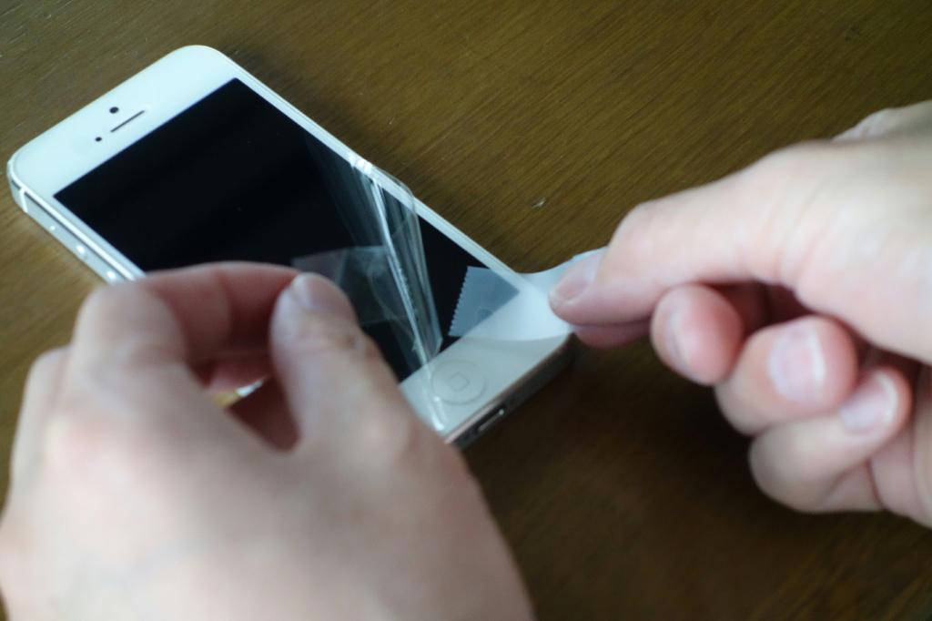 液晶保護フィルムをめくりメンディングテープでゴミの付着を取り除いている状態
