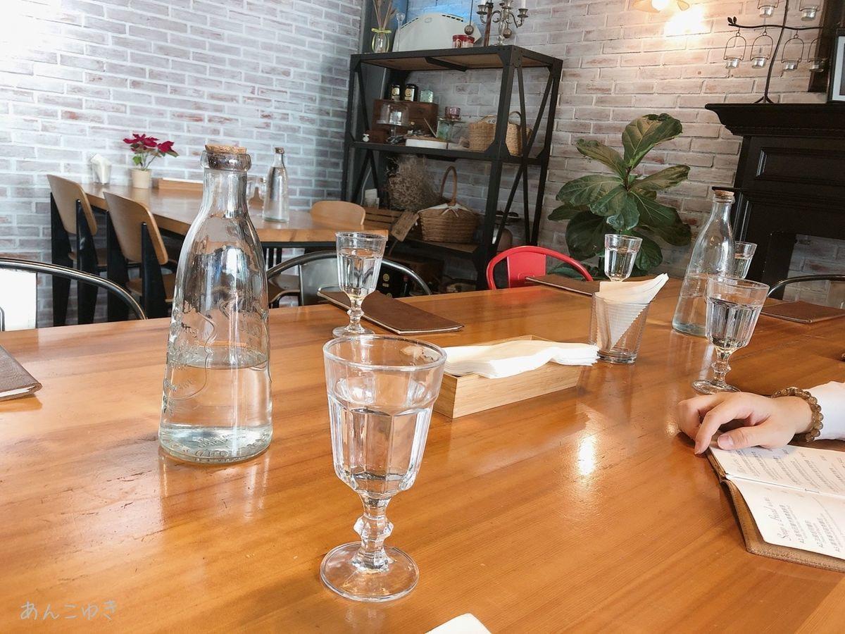 HOUSE CAFEのテーブルが写っています。水やメニューが置かれています。
