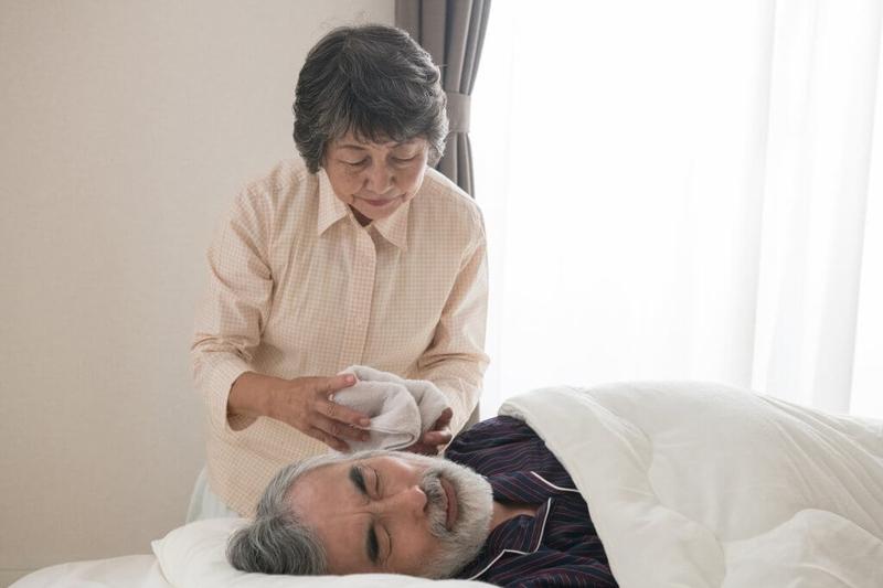 寝たきり介護をする老夫婦