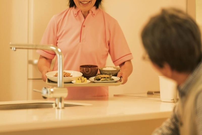 食事の配膳をする介護士