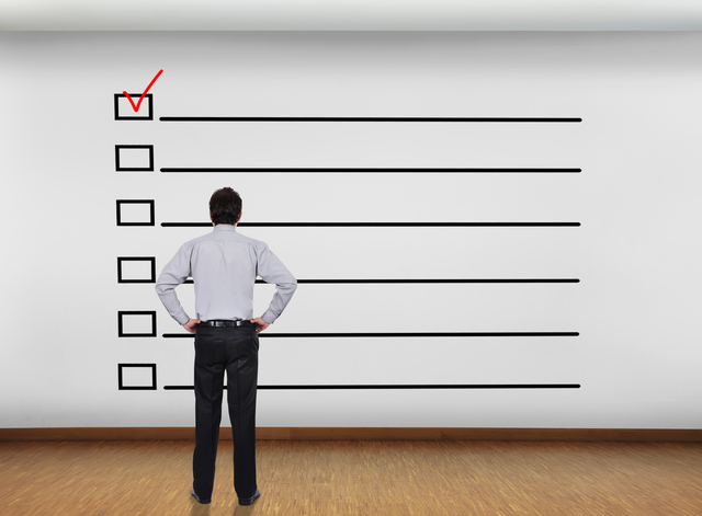 businessman in office looking at wall with checklist concept