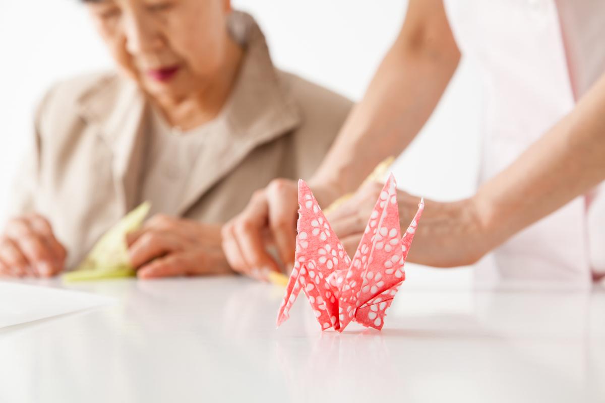 折り紙をする高齢者と介護スタッフの図
