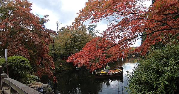 弘前公園の東内門前石橋から見たお堀に浮かぶ菊人形と紅葉の写真