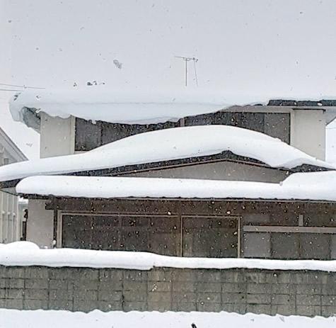 屋根に積もった雪が落ちそうな写真